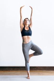 Femme sportive faisant une pose de vriksasana