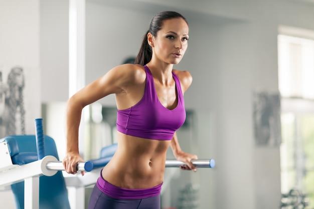 Femme sportive faisant des tractions dans la salle de gym