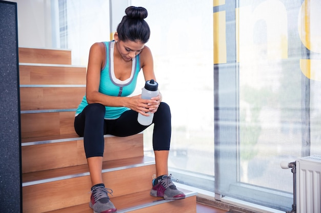 Femme sportive fatiguée assise sur les escaliers avec une bouteille d'eau dans la salle de sport