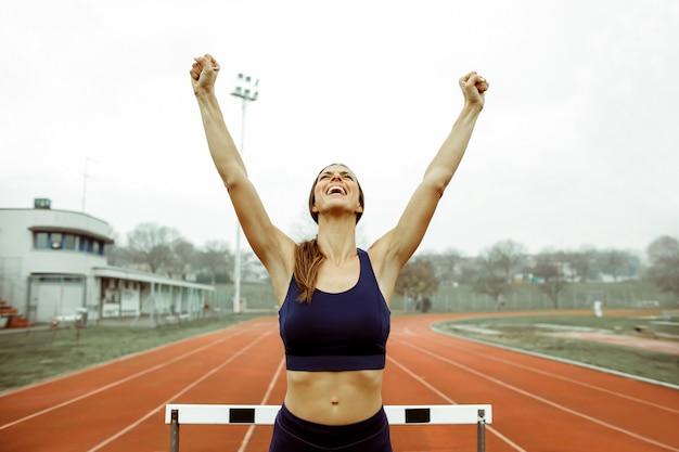 Femme sportive fête après avoir remporté une compétition de coureurs