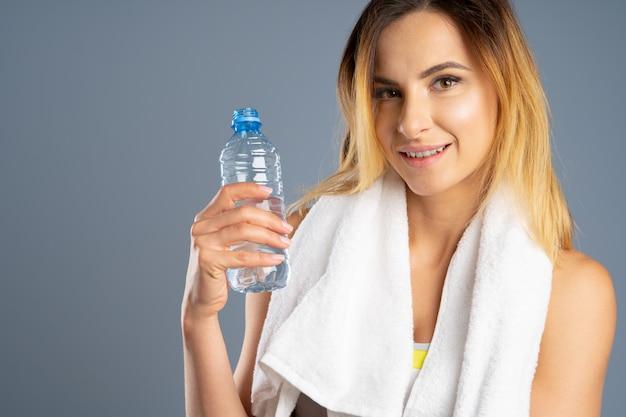 Femme sportive sur fond gris tenant une bouteille d'eau