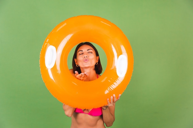 Femme sportive en forme d'été en bikini rose et anneau gonflable orange vif rond sur vert, joyeux joyeux excité joyeux positif
