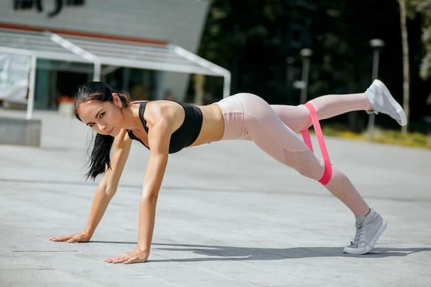 Femme sportive glorieuse faisant l'entraînement de planche avec la bande élastique de résistance