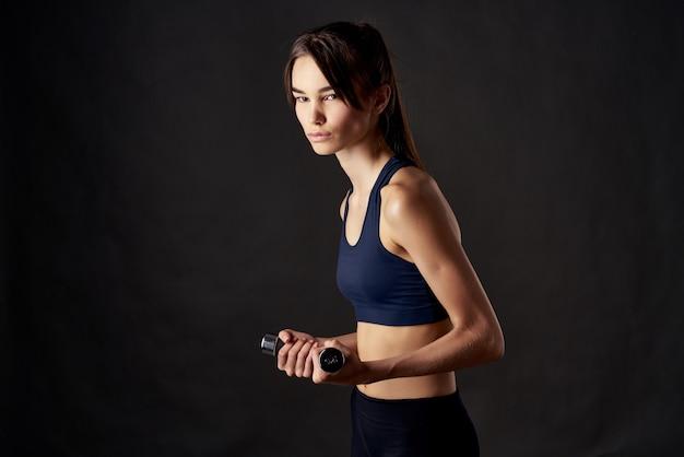 Femme sportive avec des haltères dans les mains d'entraînement fitness fond sombre