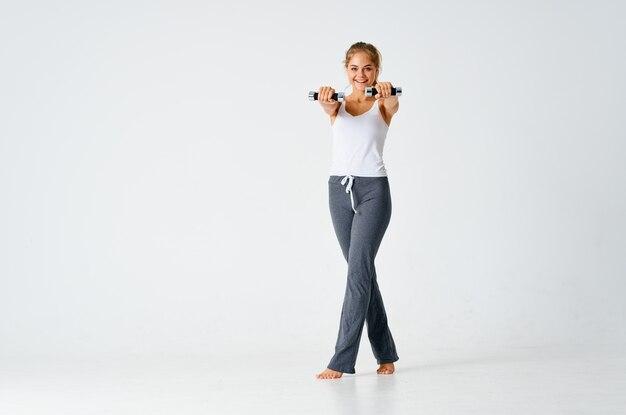 Femme sportive avec des haltères dans les mains des exercices de force d'entraînement de muscles de style de vie