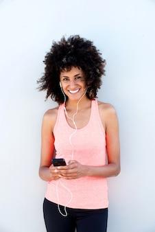 Femme sportive heureuse avec un casque tenant un téléphone mobile