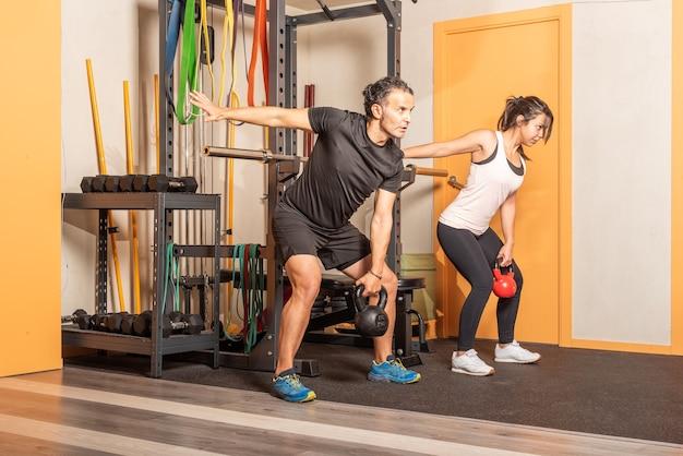 Femme sportive et homme faisant des exercices de presse à épaule avec des kettlebells en salle de sport. concept d'exercices avec équipement en salle de gym.