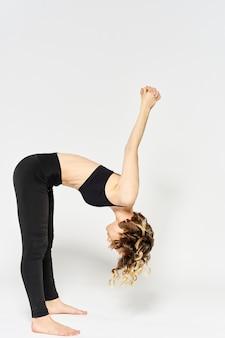 Femme sportive en jean noir et un t-shirt faisant des exercices dans une pièce lumineuse.