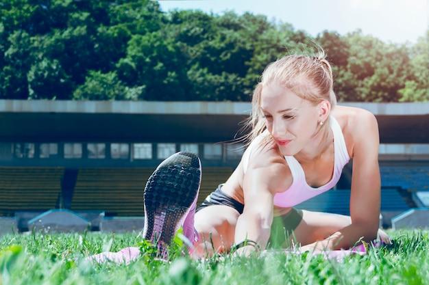 Femme sportive jeune fitness muscle faire des exercices sur le tapis rose.