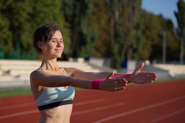 Femme sportive joyeuse faisant de l'exercice avec les mains avec une bande élastique en plein air le soir