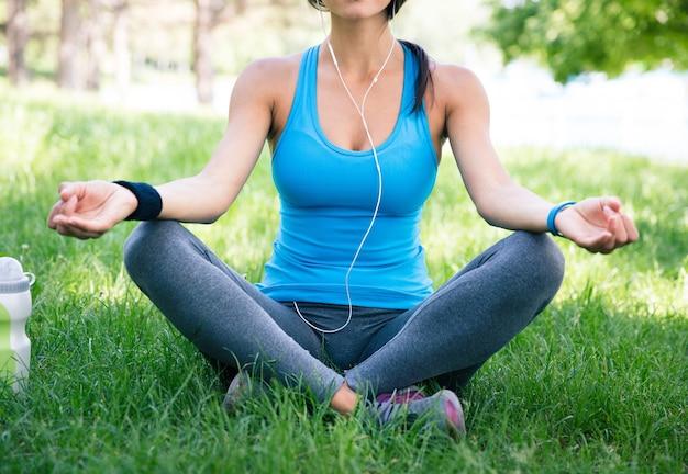 Femme sportive méditant sur l'herbe verte