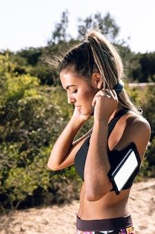 Femme sportive, mettre, sur, écouteurs