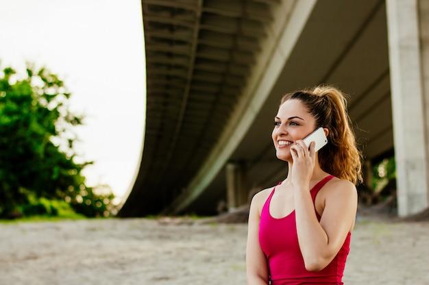 Femme sportive parlant au téléphone.