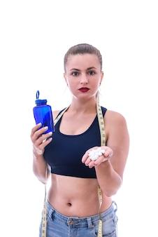Femme sportive avec des pilules et une bouteille isolée sur un mur blanc