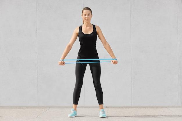 Femme sportive pleine longueur vêtue de vêtements de sport noirs, détient une bande de résistance en caoutchouc, a une séance d'entraînement à la maison, pose sur gris. gens, endurance, détermination