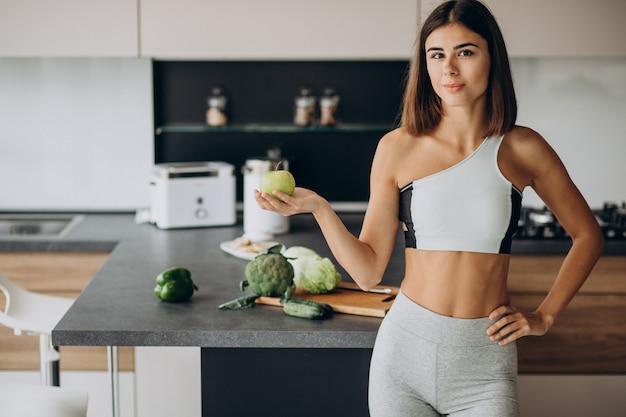 Femme sportive avec pomme dans la cuisine