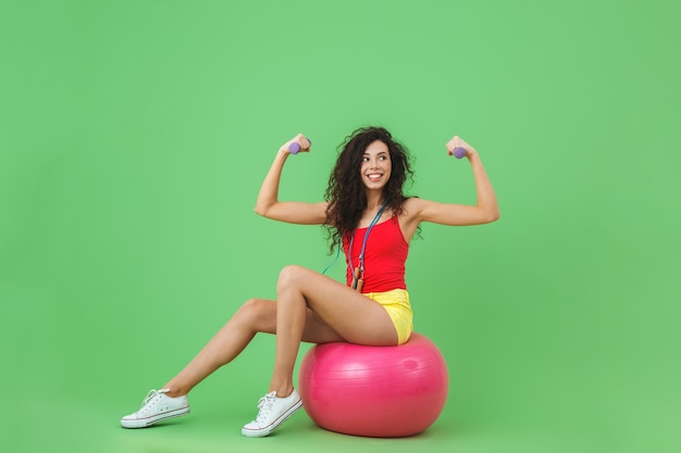 Femme sportive portant des vêtements d'été soulevant des haltères alors qu'elle était assise sur un ballon de fitness pendant l'aérobic contre le mur vert