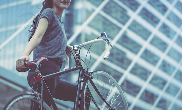 Femme sportive porte son vélo dans l'escalier