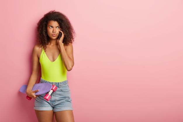 Femme sportive posant avec planche à roulettes