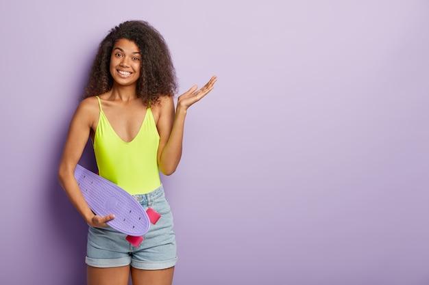 Femme sportive positive posant avec planche à roulettes