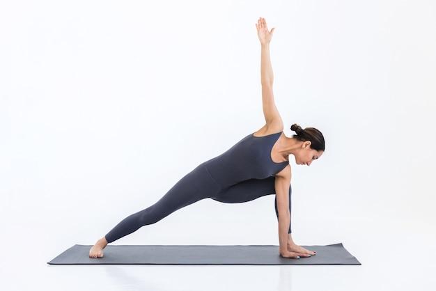 Femme sportive pratiquant le yoga sur tapis sur fond blanc faisant des étirements