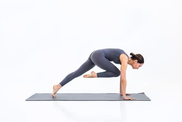 Femme sportive pratiquant le yoga sur tapis sur fond blanc en studio