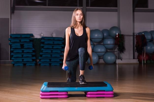 Femme sportive pratique sur plate-forme étape dans la salle de sport