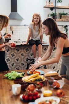 Une femme sportive prépare la nourriture, met la table avec des plats de fruits et légumes.