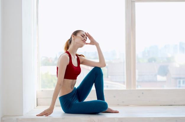 Femme sportive près de la forme physique de mode de vie de méditation de fenêtre