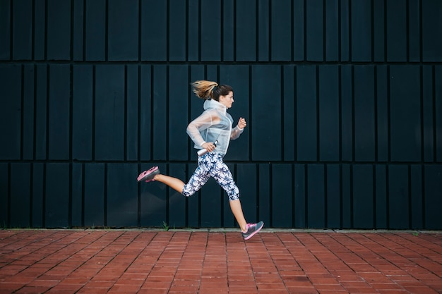 Femme sportive qui court en milieu urbain