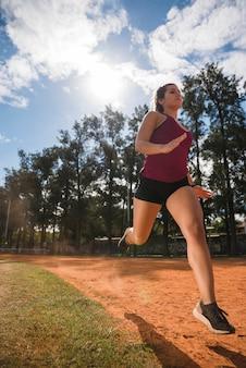 Femme sportive qui court sur la piste du stade