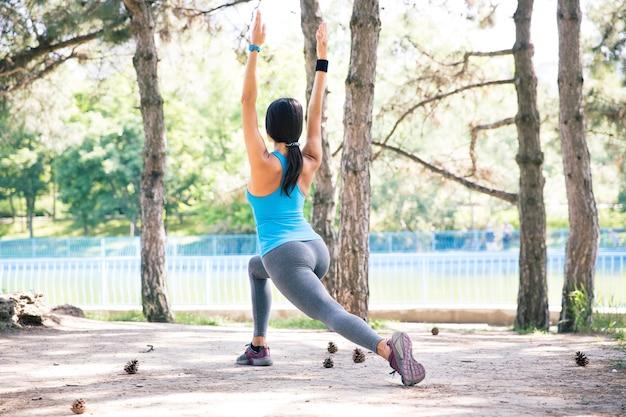 Femme sportive qui s'étend dans le parc