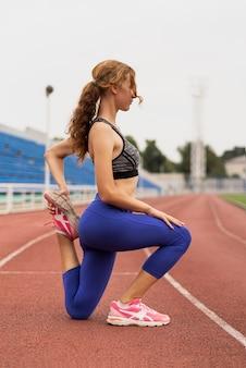 Femme sportive qui s'étend d'exercice au stade