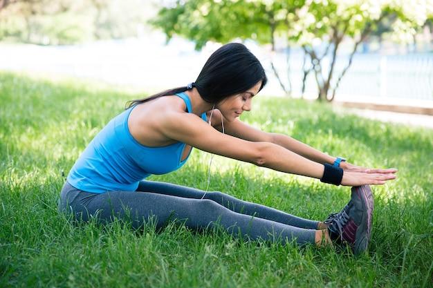Femme sportive qui s'étend sur l'herbe verte