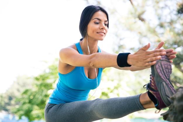 Femme sportive qui s'étend des jambes dans le parc