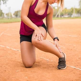 Femme sportive qui s'étend sur la piste du stade