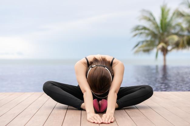 Femme sportive qui s'étend et se prépare à courir au bord de la piscine le matin.