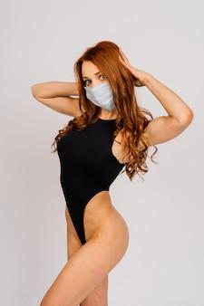 Femme sportive de remise en forme forte dans un vêtement de sport avec masque stérile. concept de mode de vie de motivation d'entraînement.