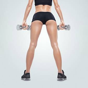 Femme sportive de remise en forme sur un vêtement de sport en formation pompage des muscles avec des haltères vue arrière