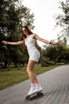 Femme sportive en robe courte et lunettes de soleil sur une planche à roulettes à l'extérieur par une belle journée d'été. heureuse jeune femme joue au surf dans le parc le matin.