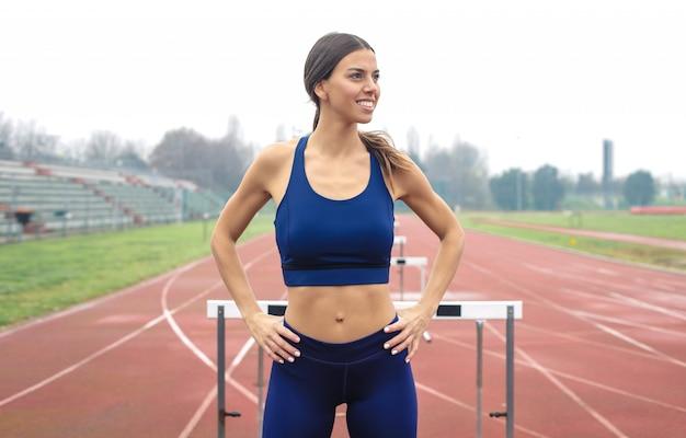 Femme sportive s'apprête à courir dans le domaine athlétique