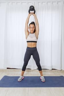 Femme sportive s'entraînant avec kettlebell pendant l'entraînement à la maison