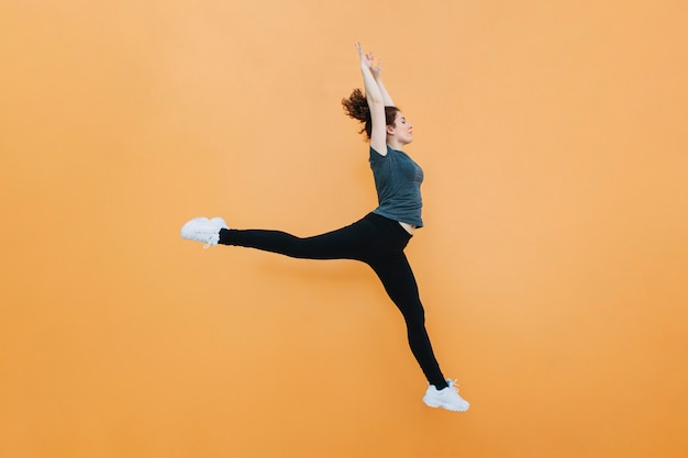 Femme sportive sautant au mur jaune
