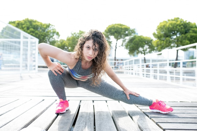 Femme sportive sexy étirant la jambe sur le pont de la ville