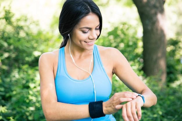 Femme sportive souriante à l'aide de montre intelligente à l'extérieur