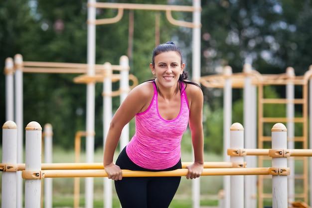 Femme sportive souriante est engagée sur une barre horizontale dans la rue