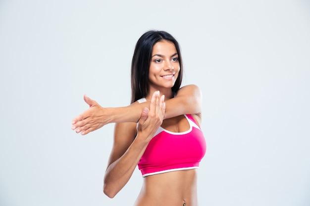 Femme sportive souriante qui s'étend des mains