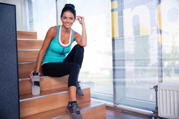 Femme sportive souriante reposant sur les escaliers dans une salle de sport avec une bouteille d'eau