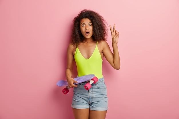 Femme sportive surprise posant avec planche à roulettes