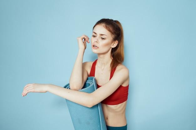 Femme sportive en tapis de débardeur rouge pour les exercices d'entraînement style de vie bleu.